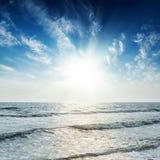 Sol i blå himmel över havet i solnedgångtid Royaltyfri Foto