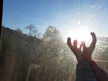 Sol i kvinnliga händer till och med skrapat exponeringsglas arkivbilder