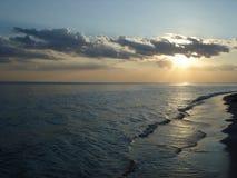 Sol i molnen på solnedgången vid havet royaltyfri fotografi