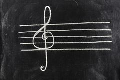 Sol key on pentagram sketched on blackboard. The music symbol of Sol key is sketched on the pentagram, with white chalk on the blackboard royalty free stock photography