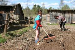 Sol lâche d'adolescente de fille utilisant des outils de jardin de main, Russie Images stock