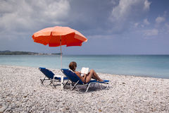Sol länge och paraply på den tomma stranden Royaltyfri Bild