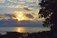 Sol levante con sole dorato con le nuvole in cielo con rivestimento sopra il mare ed i contorni dell'albero e le pietre - Neil Is fotografia stock