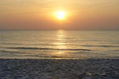Sol på himmel med havet och sand på stranden med varmt orange ljus arkivbilder