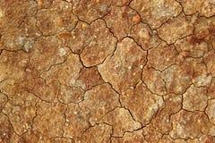 Sol pierreux brun criqué sec images stock
