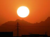 Sol poniente detrás de las montañas y de la central eléctrica Foto de archivo libre de regalías