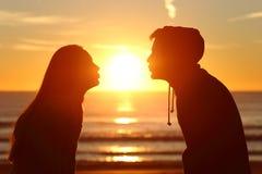 Sol que se besa de los pares con amor en la puesta del sol Imágenes de archivo libres de regalías