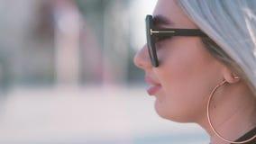 Sol que toma el sol de la mujer rubia bonita que disfruta de calor almacen de metraje de vídeo