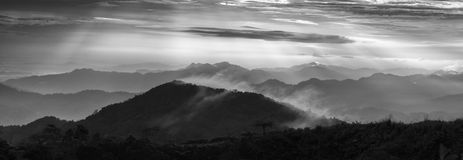 Sol-Ray skiner på berglager i svart & vit Arkivfoto