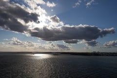 Sol som bryter till och med moln över vatten royaltyfria bilder