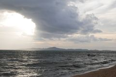 Sol som bryter till och med molnen, stund som en fiskare går tillbaka till kusten arkivfoton