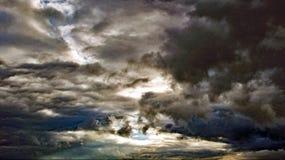 Sol som försöker att kika ut ur mörka moln Arkivbild
