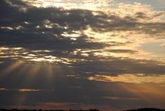 Sol som försöker att ställa in till och med molnen Arkivbild