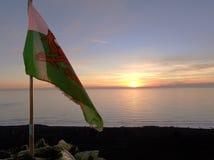 Sol som går ner bak den walesiska flaggan royaltyfri fotografi