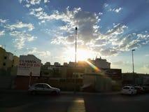 Sol som kikar över byggnader med moln royaltyfria bilder