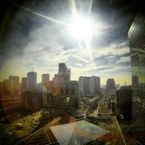 Sol som kikar i himlen över affärsmitten av en stad royaltyfri foto