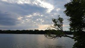 Sol som når en höjdpunkt ut ur mulen molnig himmel över sjön royaltyfri fotografi