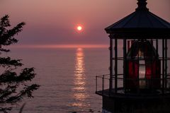 Sol som ner ställer in bredvid överkanten av den uddeMeares fyren fotografering för bildbyråer