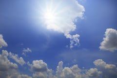 Sol som skiner över blå himmel med vitt molndagljus Arkivfoton