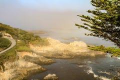 Sol som skiner på den steniga kust- och sjösidavägen arkivfoto