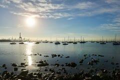 Sol som stiger över en fartygmarina med en dramatisk blå himmel Royaltyfria Foton