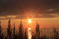 Sol som stiger över ett lugna hav Royaltyfri Bild