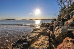 Sol som stiger över havet och blå himmel med den steniga kustlinjen arkivfoton