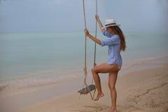 Sol- stående för sommar av mode av en livsföring av den unga stilfulla kvinnan som sitter på en gunga på stranden, bärande älskvä royaltyfria foton