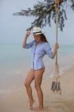 Sol- stående för sommar av mode av en livsföring av den unga stilfulla kvinnan som sitter på en gunga på stranden, bärande älskvä arkivbilder
