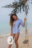 Sol- stående för sommar av mode av en livsföring av den unga stilfulla kvinnan som sitter på en gunga på stranden, bärande älskvä royaltyfri fotografi