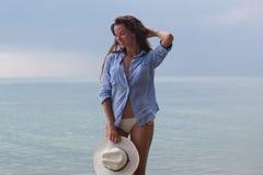 Sol- stående för sommar av mode av en livsföring av den unga stilfulla kvinnan som sitter på en gunga på stranden, bärande älskvä fotografering för bildbyråer