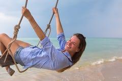 Sol- stående för sommar av mode av en livsföring av den unga stilfulla kvinnan som sitter på en gunga på stranden, bärande älskvä royaltyfri bild