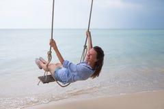 Sol- stående för sommar av mode av en livsföring av den unga stilfulla kvinnan som sitter på en gunga på stranden, bärande älskvä arkivfoton