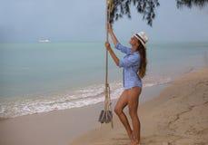 Sol- stående för sommar av mode av en livsföring av den unga stilfulla kvinnan som sitter på en gunga på stranden, bärande älskvä arkivbild