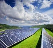 Sol- station i grönt fält under blå molnig himmel med berget Arkivfoton