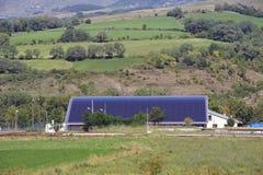 Sol- tak av en stor krökt yttersida på en kommunal byggnad arkivbild