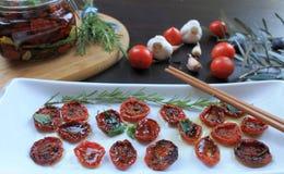 Sol-torkade körsbärsröda tomater med kryddor i olivolja i en glass krus Royaltyfria Bilder
