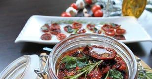 Sol-torkade körsbärsröda tomater med kryddor i olivolja i en glass krus Arkivfoto