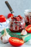 Sol-torkade tomater med vitlök, kryddor och olivolja royaltyfri bild