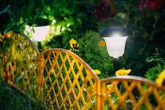 Sol- trädgårdljus, små dekorativa lyktor i blomrabatt gar fotografering för bildbyråer