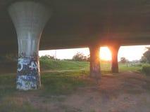 Sol a través de los pilares del puente Imagen de archivo libre de regalías