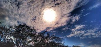 Sol under älskvärda moln fotografering för bildbyråer