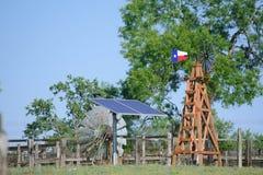 Sol- vatten väl med Texas Windmill som är främst av sommargräsplanträd, lantgårdranchstaketet och bakgrund för blå himmel Royaltyfria Bilder