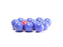 Sola bola roja y bolas azules Imagen de archivo