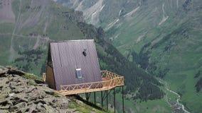 Sola casa de madera con un tejado rojo en un alto de la colina en las montañas con una hermosa vista del valle verde en un solead almacen de video