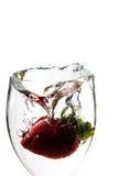 Sola fresa que cae en el agua Imágenes de archivo libres de regalías