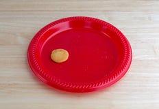 Sola galleta de la vainilla en una placa roja Fotos de archivo