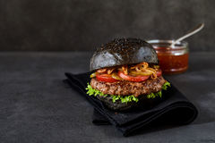 Sola hamburguesa con los bollos del pan negro Imagen de archivo libre de regalías