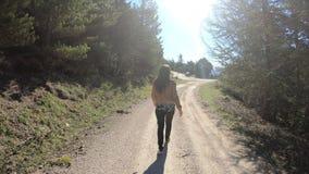 Sola mujer joven que camina en una trayectoria en los Pirineos, Francia