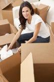 Sola mujer que desempaqueta los rectángulos que mueven la casa Imagen de archivo libre de regalías